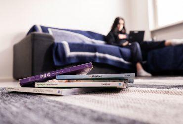 Tyttö istuu sohvalla tietokone sylissä ja etualalla lattialla on kasa koulukirjoja.