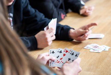 Nuoret pelaavat pelikorteilla.