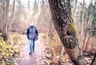 Haastavana aikana yksinäinen mies kulkee metsässä maski kasvoilla